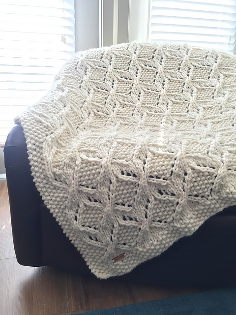 Hand knitted blanket laid over a chair