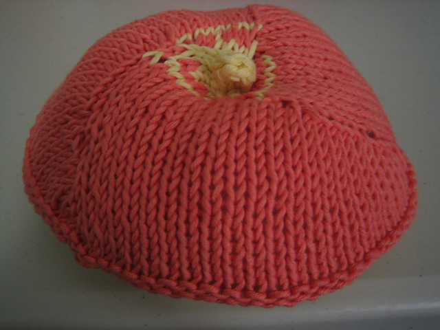 a C cup titbit knit from peach cotton with a yellow nipple, resting on a grey tabletop