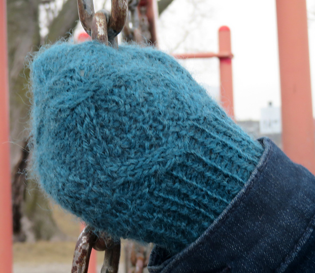 Someone wearing a cabled mitten and gripping a chain. The mitten cables enclose a section of double moss stitch.