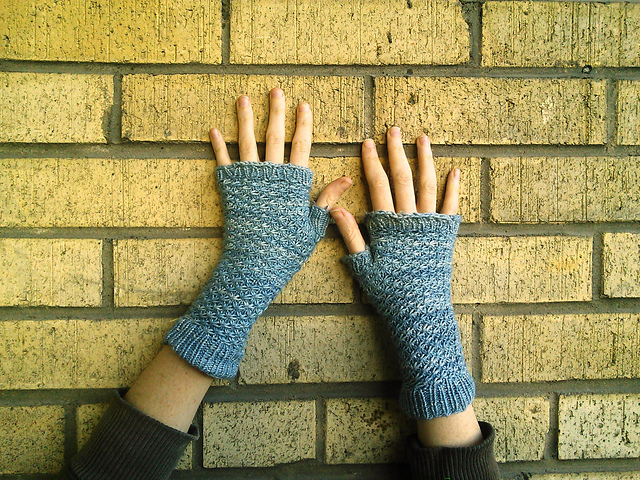 a pair of blue fingerless mittens in a textured pattern being worn and displayed against a brick wall.