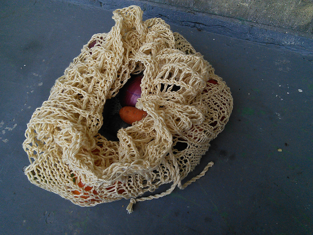 A mesh market bag with a half-open drawstring top.