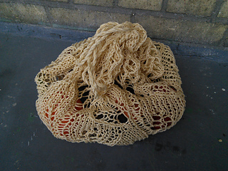 A mesh market bag with a few vegetables inside. It's been tied off at the top with a twisted cord drawstring.