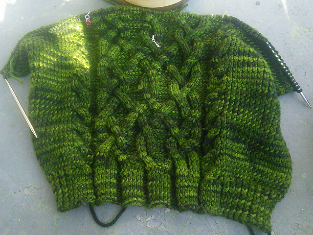 A peice of knitting laying flat, still live on a circular needle.  There's a large central cable motif and two smaller cables on either side.  The knitting is done in a tonal yarn that varies between emerald green and almost black.