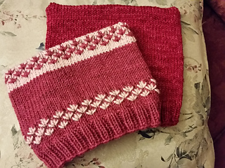 Two dark pink pussy hats, one with light pink trinity stitches