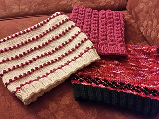 Three pink pussy hats in various textured patterns