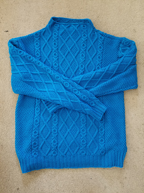 Bright blue knit sweater with a cabled design.