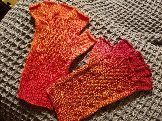 Fingerless gloves in red and yellow yarn, with a delicate twisted stitch pattern